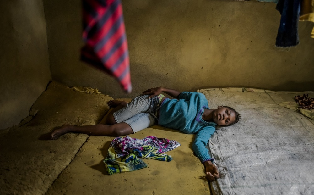 Isatu Sesay, 16, suffering from symptoms of Ebola rolls around delirious and in pain, 3 hours before her death in the community of Kissi Town in Freetown, Sierra Leone. November 21, 2014 © Daniel Berehulak for The New York Times