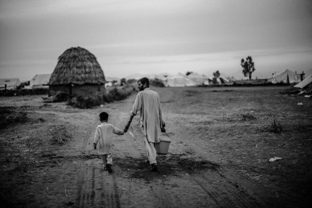 A man and a boy, internally displaced from the Pakistan Army's offensive against the Taliban in Swat and Buner, walk back to their tent after having collected water at a nearby canal at the Yar Hussain UNHCR camp in Chota Lahore in Swabi, Pakistan. May 18, 2009. © Daniel Berehulak/Getty Images
