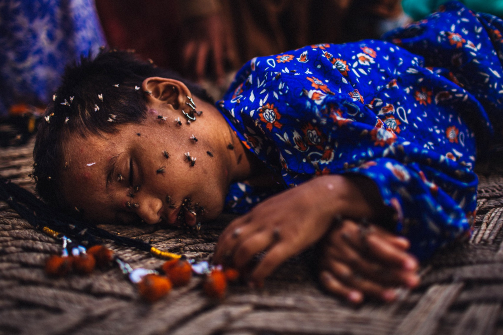 A young girl, displaced by floods, sleeps covered in flies on a makeshift bed in Garhi Khairo, Pakistan. August 27, 2010 © Daniel Berehulak/Getty Images