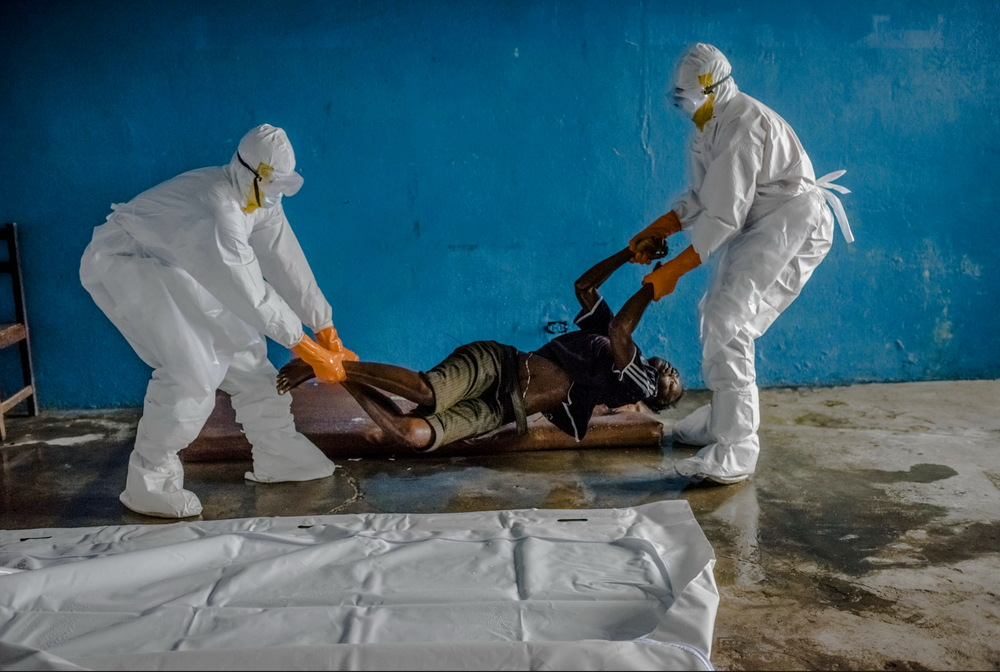 A Liberian Red Cross burial team wearing protective clothing retrieve the body of Edwina Doryen, 24, who tested positive for Ebola and died in the Ebola isolation ward, a closed down school, in the Westpoint neighborhood in Monrovia, Liberia. August 28, 2014  © Daniel Berehulak for The New York Times