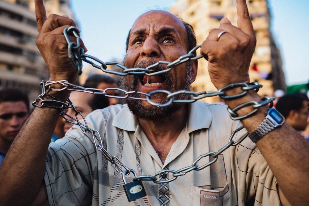A man bound in chains chants anti-Shafiq slogans as other Egyptian supporters of the Muslim Brotherhood celebrate a premature victory for their presidential candidate Mohamed Morsi in Cairo, Egypt. June 18, 2012 © Daniel Berehulak/Getty Images