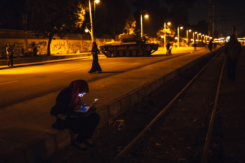 An Egyptian woman types on her laptop prior to the start of a demonstration opposing president Mohammed Morsi at the Presidential Palace in Cairo, Egypt. December 18, 2012  © Daniel Berehulak/Getty Images