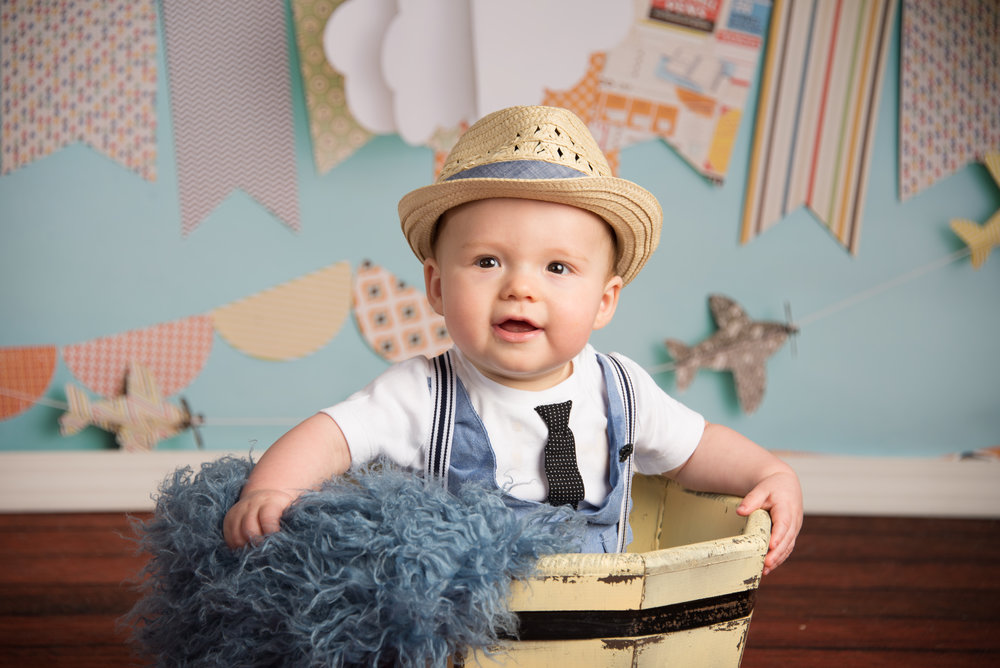 six month boy in hat sitting in bowl