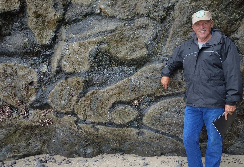Field trip leader, GSOC President Bo Nonn, posing next to some pillow basalts at Arcadia Beach.