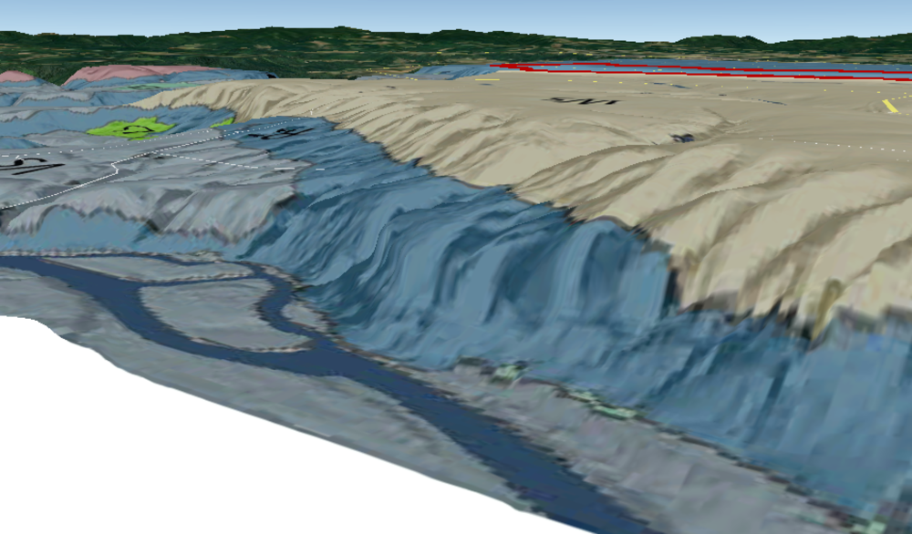 View of plateau from sandy river showing layer of river rock (blue) and Loess (cream).
