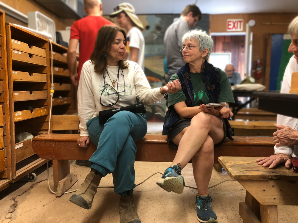 Board members Dawn Nilson (RCA) and Carol Hasenberg (GSOC) gather in Lon's Lab for Orr's Fossil ID session. Photo by Paul.