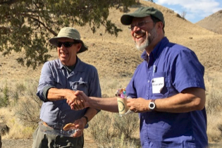 Bob Timmer and Paul Edison-Lahm perform the ceremonial handshake and exchange of GSOC mug during the GSOC/COGS get-together. Photo by CSH