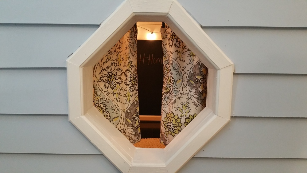 Pretty little octagonal window with kid-sized curtains!