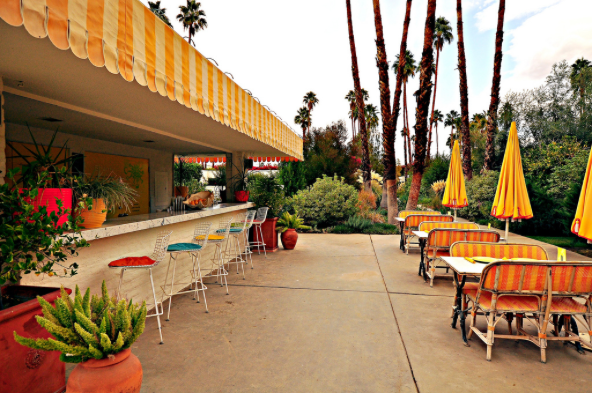 In a slight departure from the modern midcentury look, their outdoor pool bar is decorated with wicker benches and sunny yellow umbrellas reminiscent of the 40s and 50s.