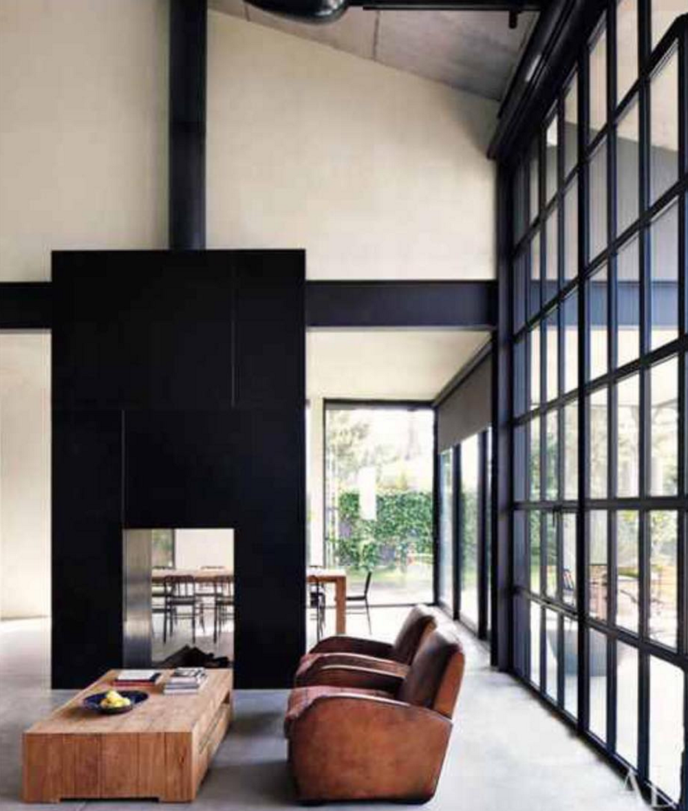 The sleek lines and prominent placement of this modern industrial fireplace make it a showstopper.  Love the warmth that the leather chairs bring.