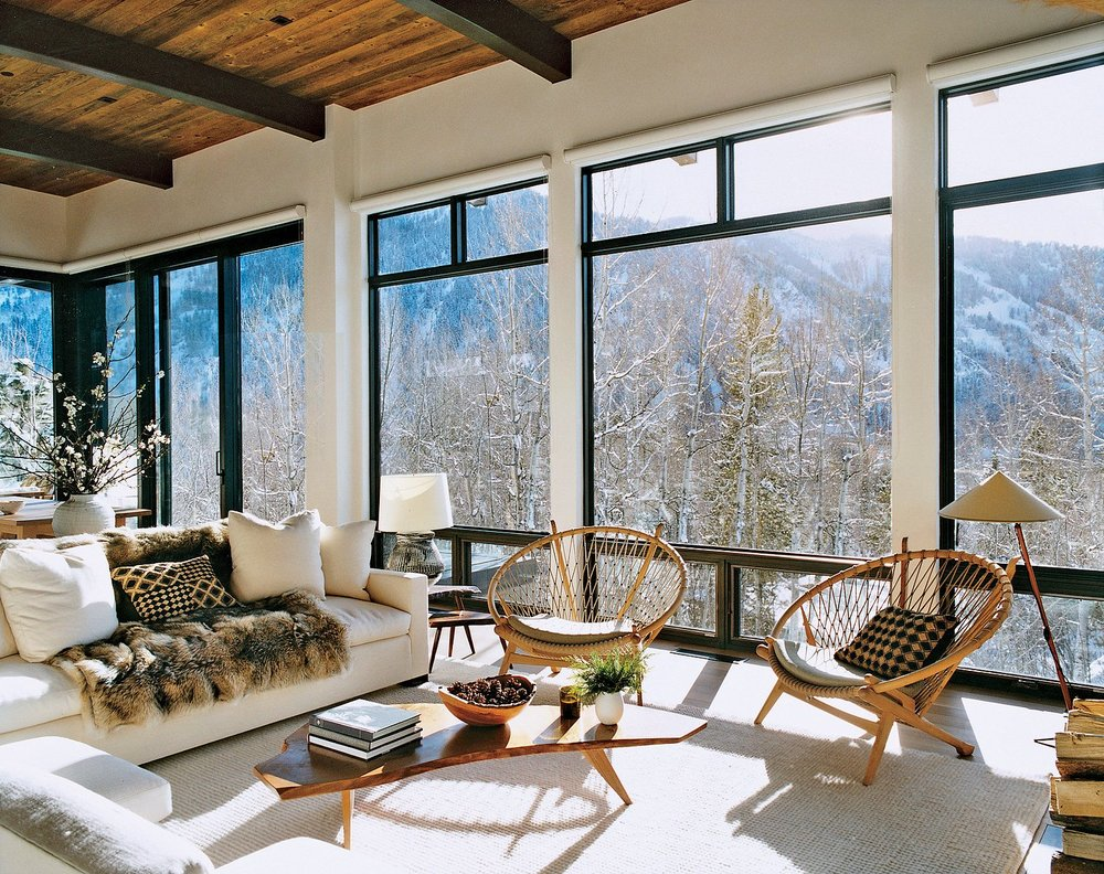 Aerin Lauder's light-filled Aspen living room combines an ecclectic mix of classic furniture and midcentury modern.  The live edge coffee table with wooden hairpin legs is out of this world!