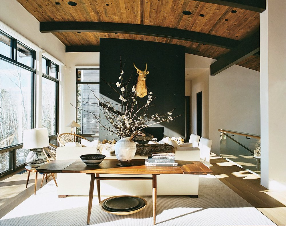 From the alternate view, her George Nakashima table is the perfect nesting spot for a beautiful centerpiece arrangement and books.  And the gold-plated faux deer heed creates a natural balance that works well with the interior.