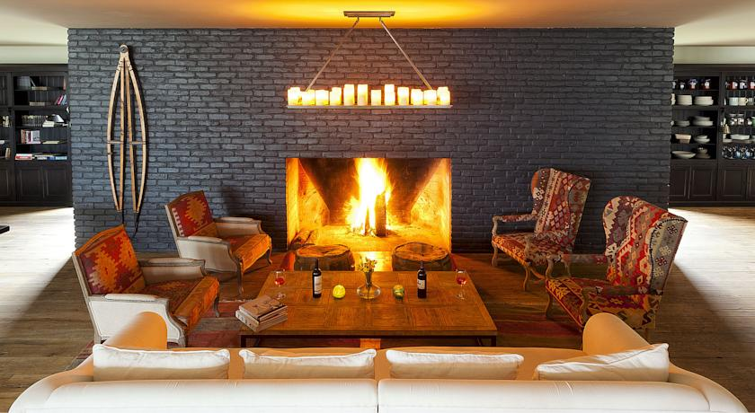 Enjoying a nightcap on wayuu printed chairs next to the dark brick fireplace feels oh so chic.