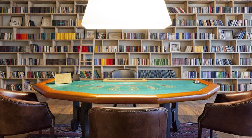 This poker table is perfectly placed among library-style bookshelves.