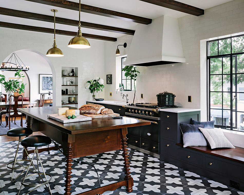This modern Mediterranean kitchen serves up a unique mix of Safavieh style wood island and Moroccan tiles.  I've always been a fan of dark blue kitchen cabinets and this one is no exception.  The brass pendant lights help warm of the dark tones.  Wishing I could spend every Saturday in this kitchen.