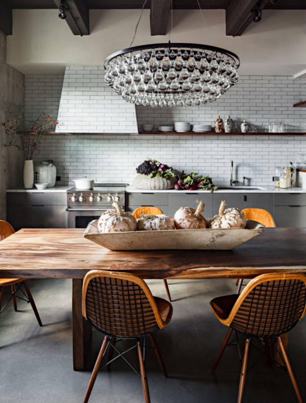Swoon. Love the texture in this room -- the threaded Eames dining chairs, the milky way patterns on the rustic dining, and the gorgeous subway tiles. The squash centerpiece is the perfect decorative touch for Fall.