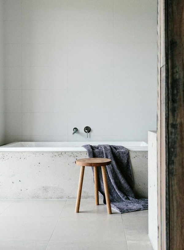 This modern boho tub with a texture-rich exterior is lightly glazed inside for comfort.  The rustic stool is the perfect stand for wine and books during bathtime.