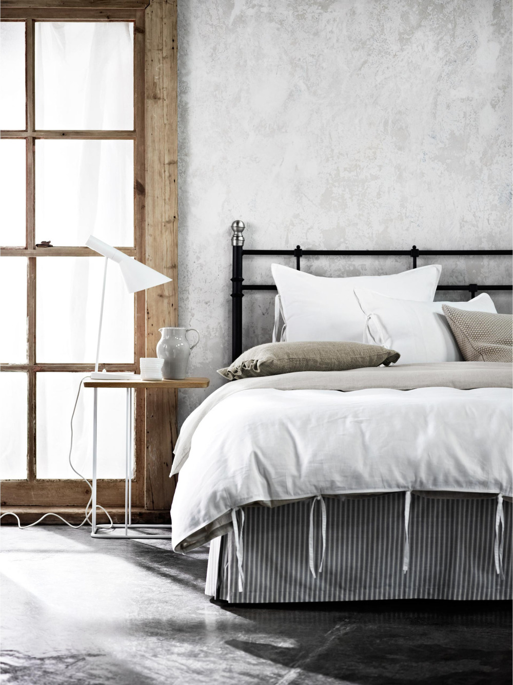 For those who aren't ready to dial it up to a 10, opt for a neutral tone ticking stripe bedskirt over earthy bedding and pillows.  The rustic window frame and nightstand completes the look perfectly.
