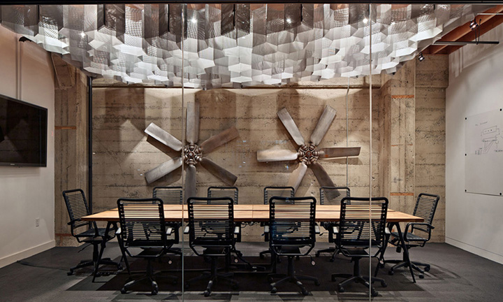 This industrial office uses real airplane propellers against a concrete wall to create authenticity.  The Herman Miller office chairs surrounding the boardroom table up the wow factor.