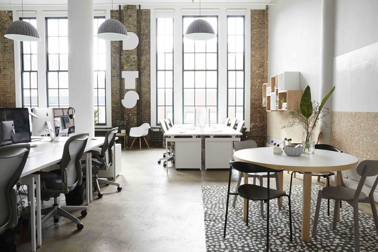 Dots grey and white office with high ceilings and natural light creates an elegant design for its game makers.