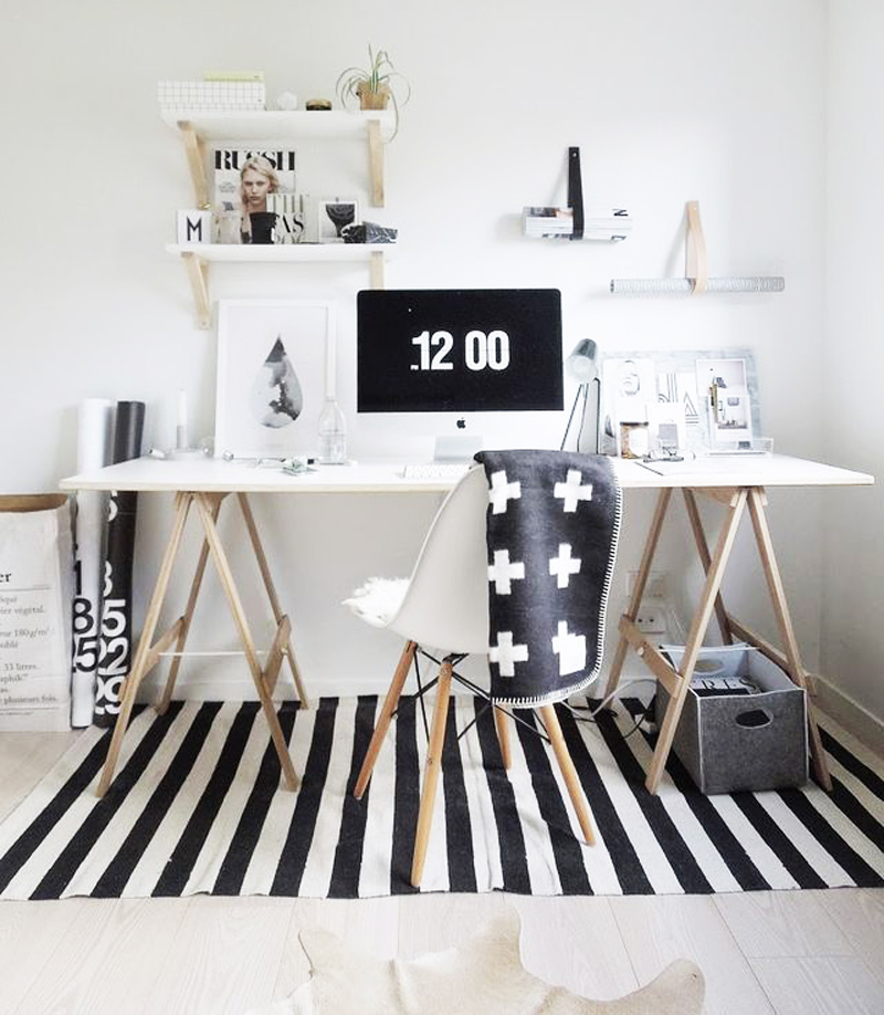 This light office keeps it cozy with a black and white cross blanket and matching rug.  The sawhorse legs look beautiful with this style.
