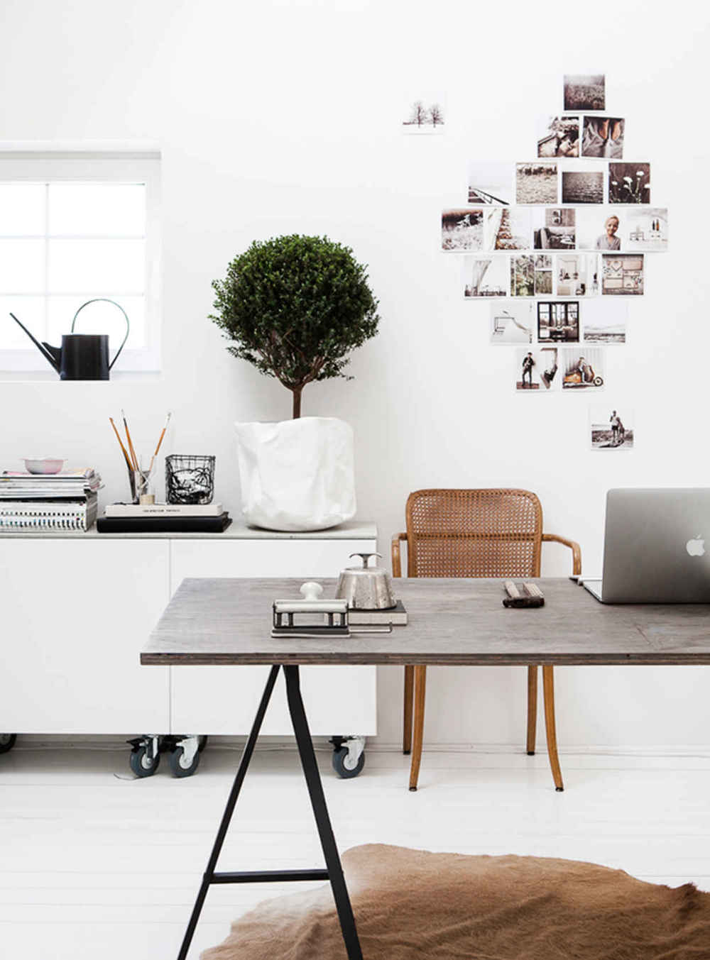 In one word...obsessed! From the rattan chair and the cowhide rug, to the potted boxwood plant and collage style photos, this office is perfection!
