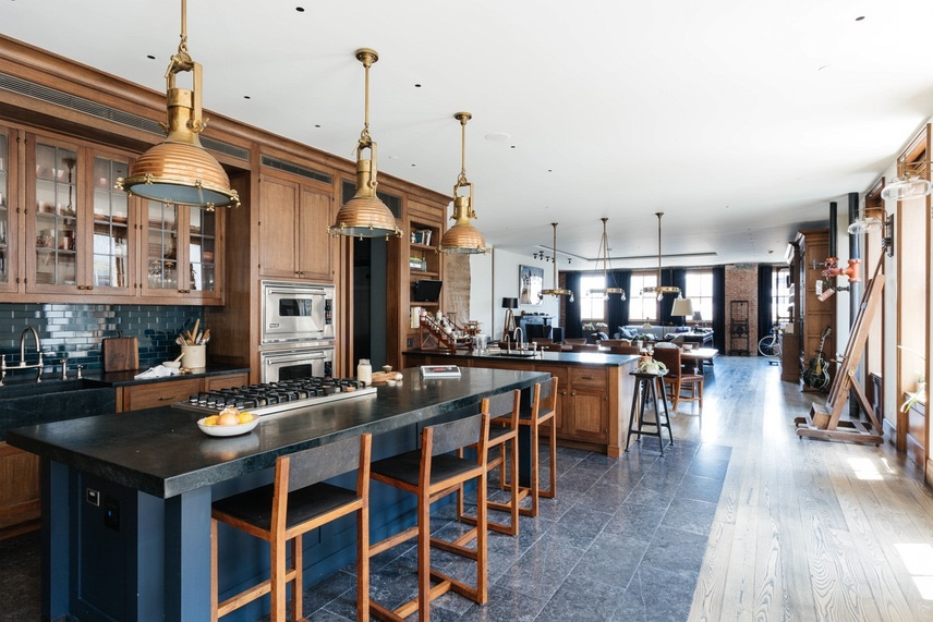Industrial kitchen, brass pendant lighting and original exposed brick are some of the charms of this chic TriBeCa New York loft.