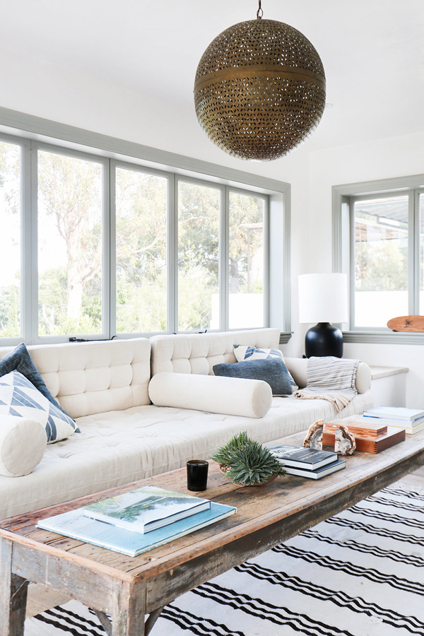This family room is meant to lounge around in.  The coffee table is perfectly balanced with decorative accents breaking up the stacked coffee table books.