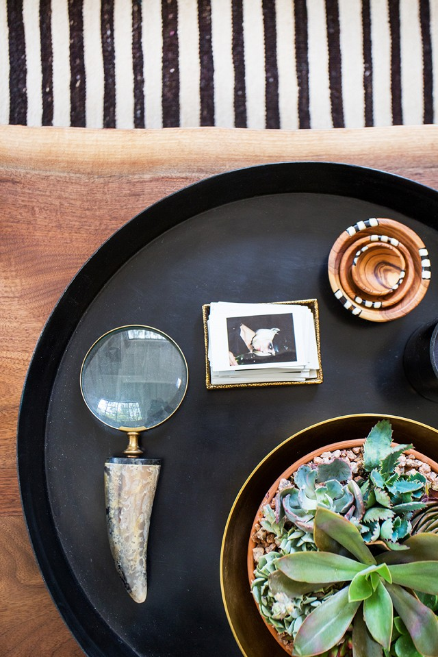 Forget coffee table books.  Try cute accessories like these on a dark round tray to give your home a one-of-a-kind feel.