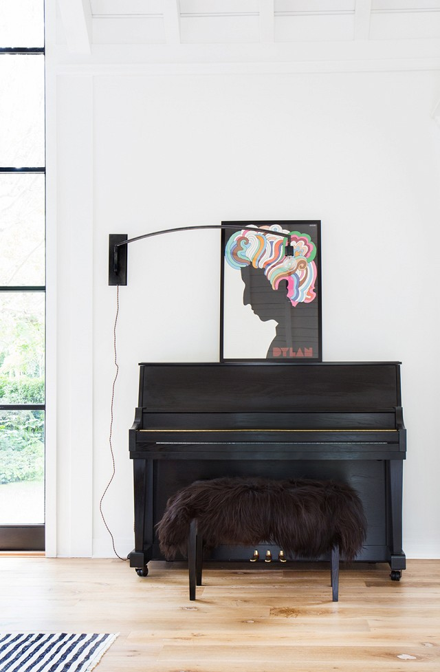 The Bob Dylan framed poster above the black piano is the perfect functional piece for entertaining in this home.