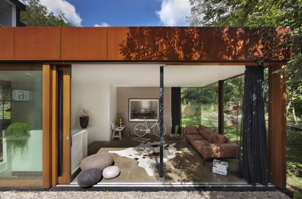 The modern exterior with floor to ceiling windows and sliding glass doors provide a peek into this stylish Dutch home.
