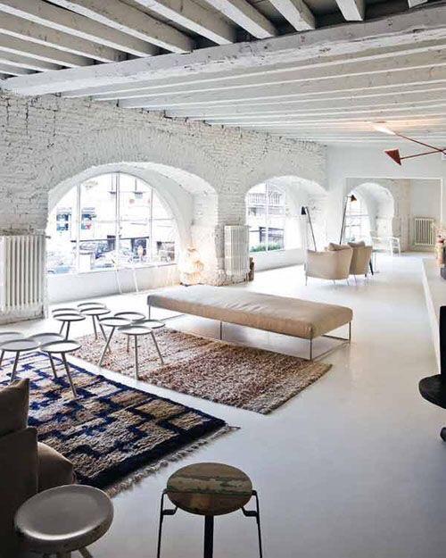 Berber rugs and rustic stools accessorize this white washed brick loft spectacularly!