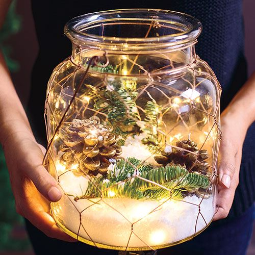 Add a lantern a custom lantern to you table for instant mood lighting.  I love this hurricane filled with Christmas lights, faux snow, pine cones and tree clippings to set the scene.  For additional rustic flair, wrap it in chickenwire.