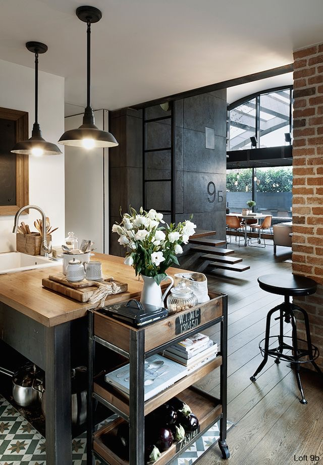 This is the cutest industrial kitchen I've ever seen.  I love how the white flowers make it feel like a home.