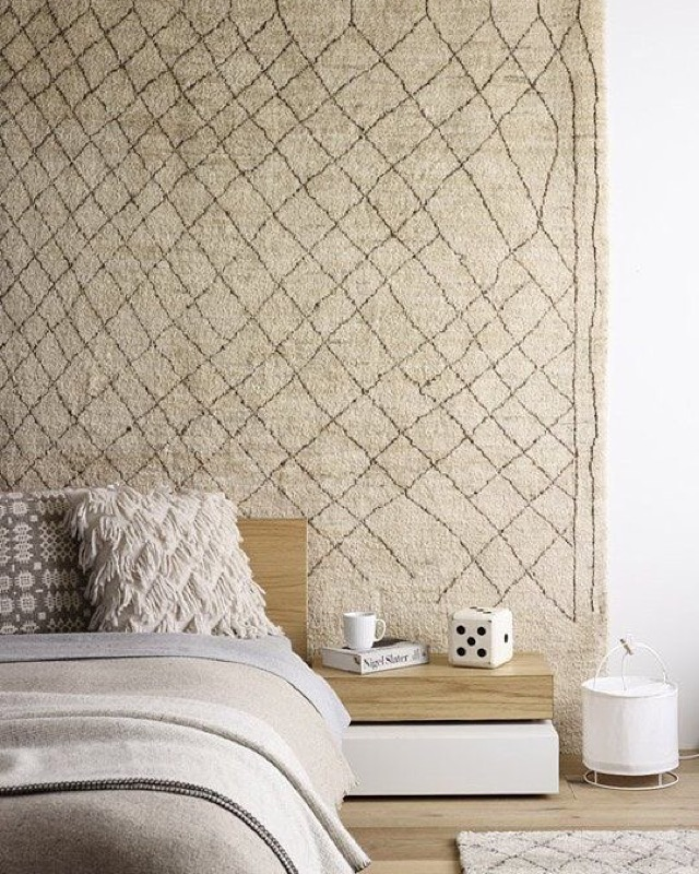 A geometric tapestry rug helps to give this bedroom extra dimension.