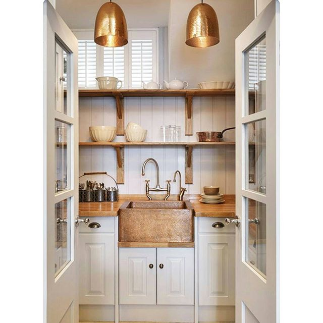 This white farmhouse kitchen mixes traditional design with modern open shelving.