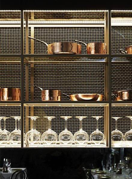 The dark backsplash, backlighting and copper pots make this the most glam kitchen I've ever seen.