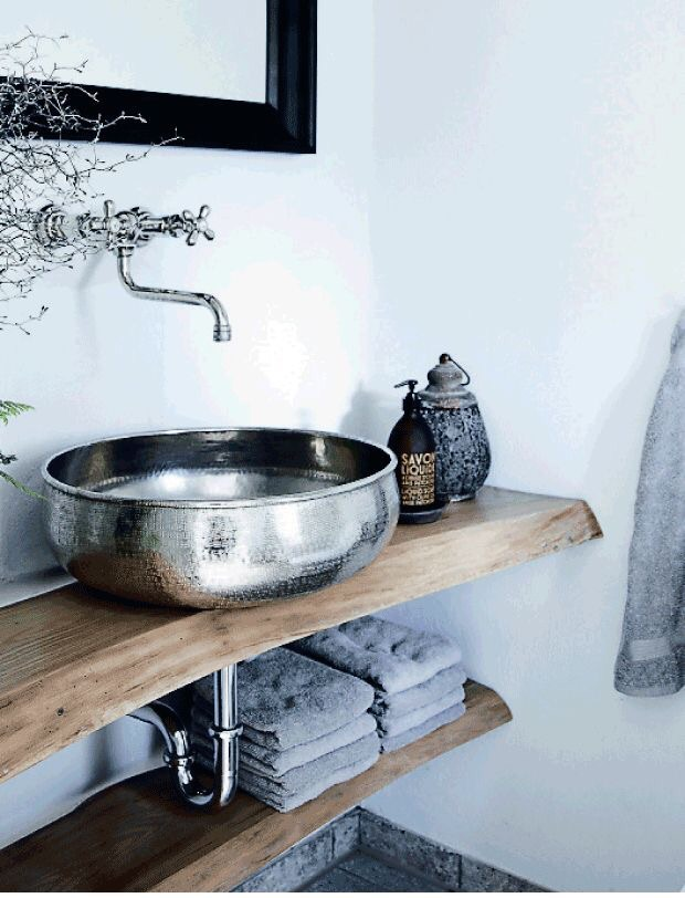 Organic modern bathrooms always pair minimalism with rustic appeal.  I love this Moroccan inspired nickel vessel sink and live edge wood counter in the bathroom.
