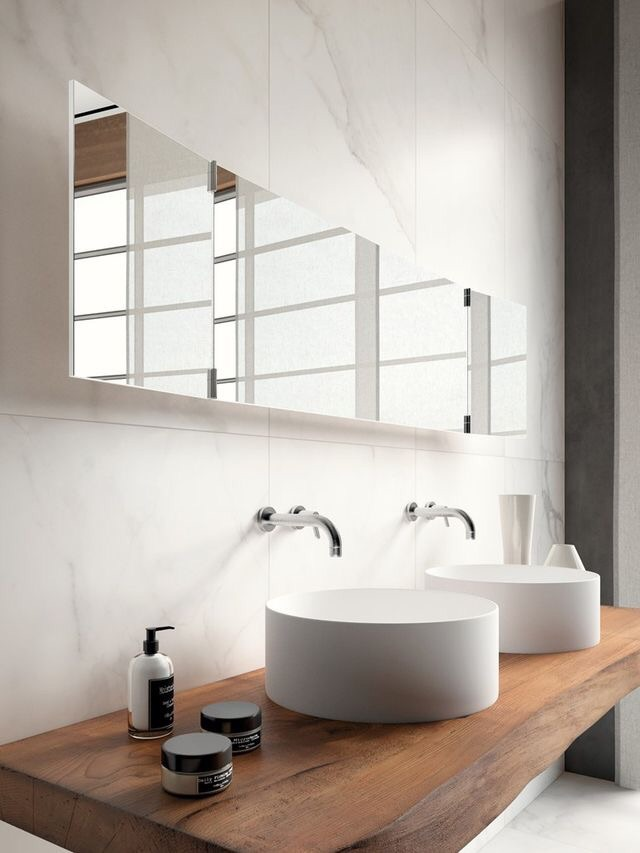 These round modern vessel sinks contrast perfectly with the live edge wood shelves.
