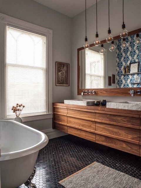 This modern boho bath feels so chic with dark hexagonal tiles, rustic cabinets, blue Ikat wallpaper, and industrial pendant lights that reimagine your typical vanity lights.