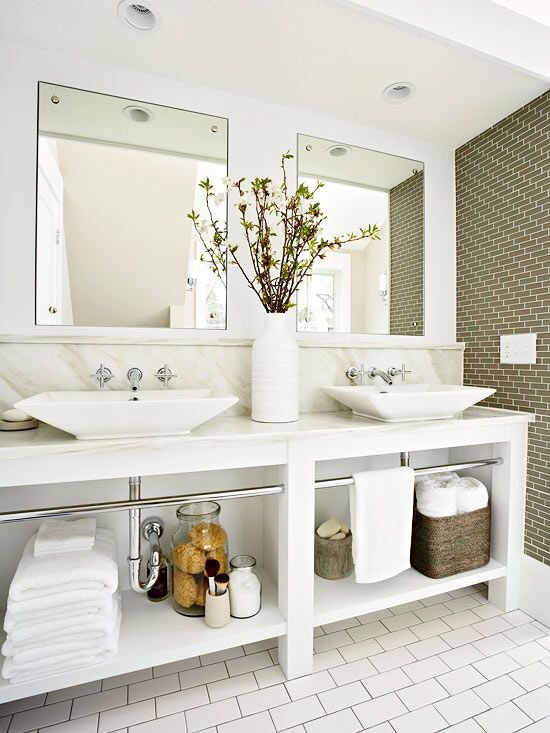 This traditional bathroom uses soothing green subway tiles and recessed lighting feel ultra high end.