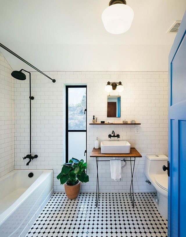 This updated Victorian bathroom highlights its best features with black and white floor tiles and pairs it with a black showerhead, modern vanity, and stylish blue door.