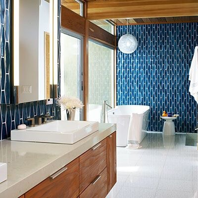 This midcentury modern blue tiled bathroom includes luxe upgrades as a soaking tub and oak cabinets with slim pulls.