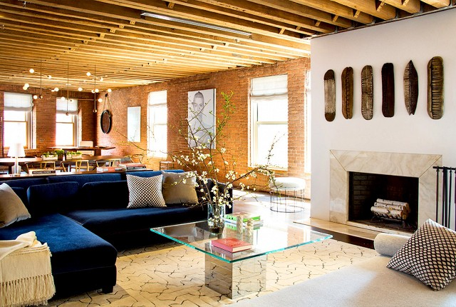 This loft is so expansive and open.  I wish all living rooms could have these high ceilings and beams like this space.