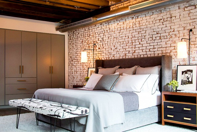 I love how the bedroom mixes up the patterns of the exposed brick, bench, and midcentury modern bedside table.
