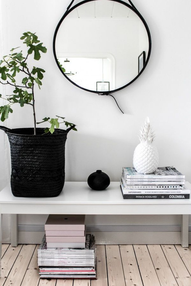 This monochromatic entryway keeps it simple with a lovely basket planter, some magazines (now you know what to do with them), and industrial mirror.