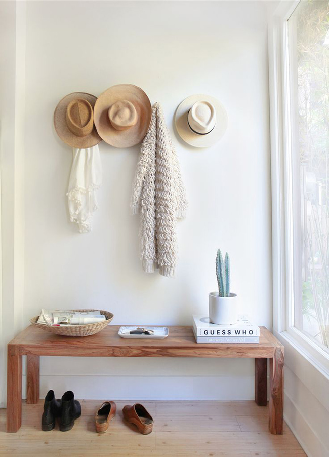 This entryway look is easy to pull off with a rustic bench, coat hooks, and succulents.