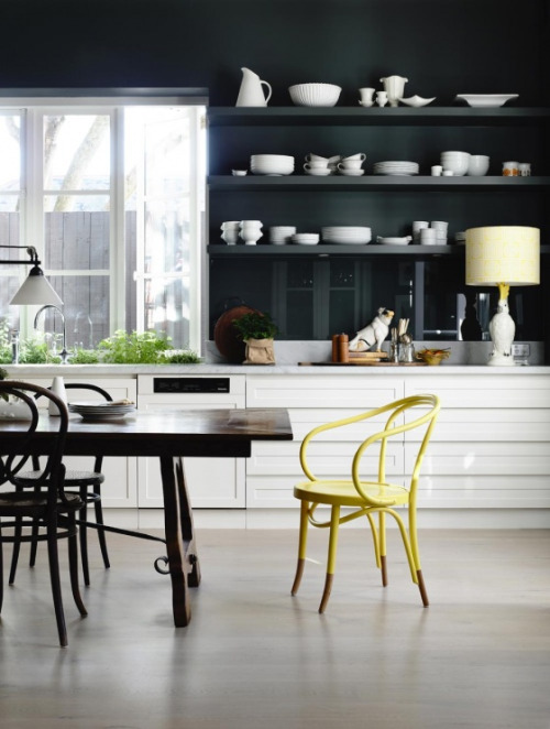 I love how this dark blue kitchen lightens the mood with white countertops and a pop of yellow.