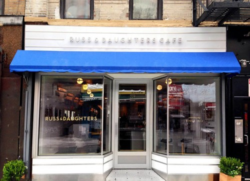 Russ & Daughters Cafe's white trimmed exterior with blue awning creates an inviting restaurant front.