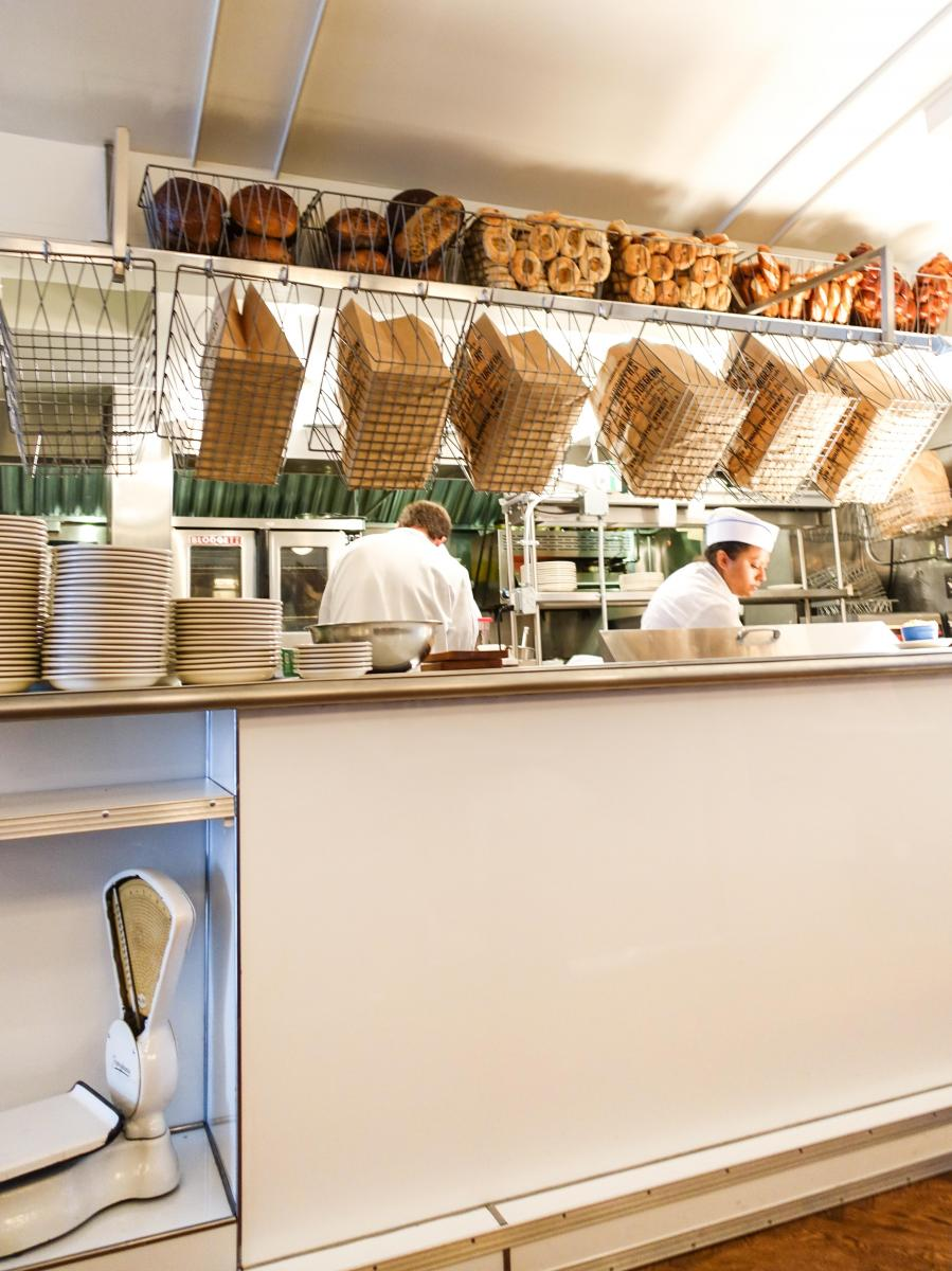 Baskets of fresh bagels hang above the kitchen for chefs to grab quickly.